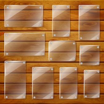 Zestaw przezroczystych szklanych talerzy o różnych kształtach, przykręconych do drewnianych desek