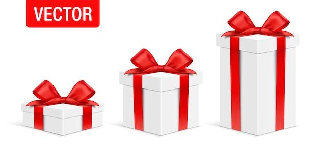 Zestaw pudełek prezentowych w kolorze białym o różnej wysokości, z czerwoną satynową kokardką, na białym tle na białym tle.