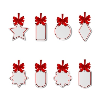 Zestaw pustych świątecznych białych metek z czerwonymi kokardkami i wstążkami