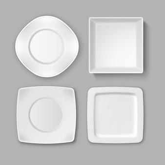 Zestaw różnych pustych kwadratowych białych talerzy i miski na białym tle na szarym tle, widok z góry