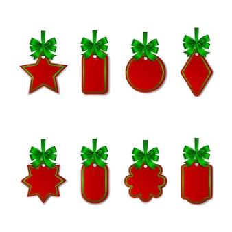 Zestaw świątecznych pustych czerwonych metek z zielonymi kokardkami i wstążkami na białym tle tagów prezentowych