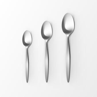 Zestaw sztućców srebrny łyżka stołowa łyżka deserowa i łyżeczka do herbaty widok z góry na białym tle. ustawienie stołu