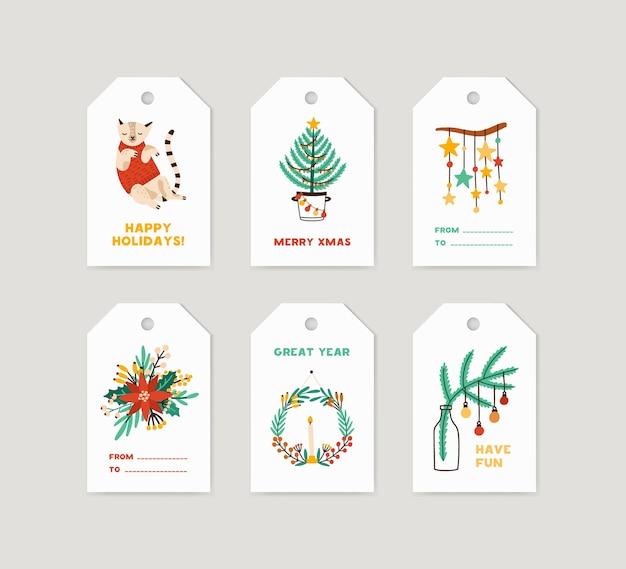 Zestaw tagów ferii zimowych. etykiety świąteczne ozdobione sosną, wieńcem bożonarodzeniowym, sezonowymi kwiatami i uroczym kotem na białym tle. gratulacje noworoczne, kolekcja kart okolicznościowych merry xmas.