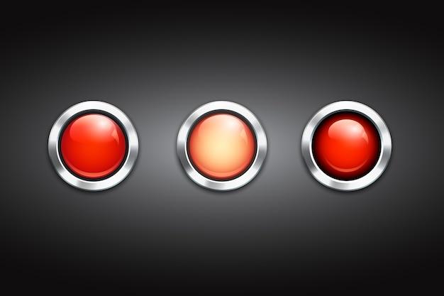 Zestaw trzech pustych czerwonych guzików z błyszczącymi metalowymi krawędziami i refleksami