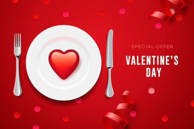 Zestaw walentynkowy z czerwonym sercem na talerzu i sztućcach.