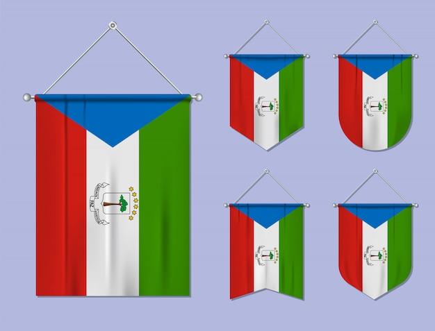Zestaw wiszących flag gwinei równikowej z tekstylną teksturą. różnorodność kształtów kraju bandery. proporczyk pionowy szablon