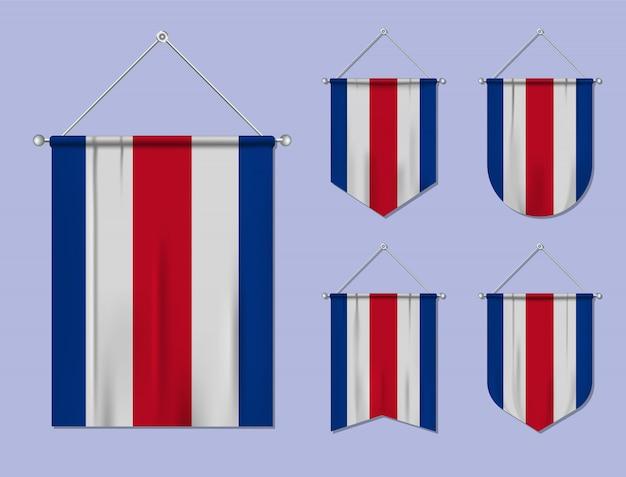 Zestaw wiszących flag kostaryki z tekstylnymi teksturami. różnorodność kształtów kraju bandery. proporczyk pionowy szablon