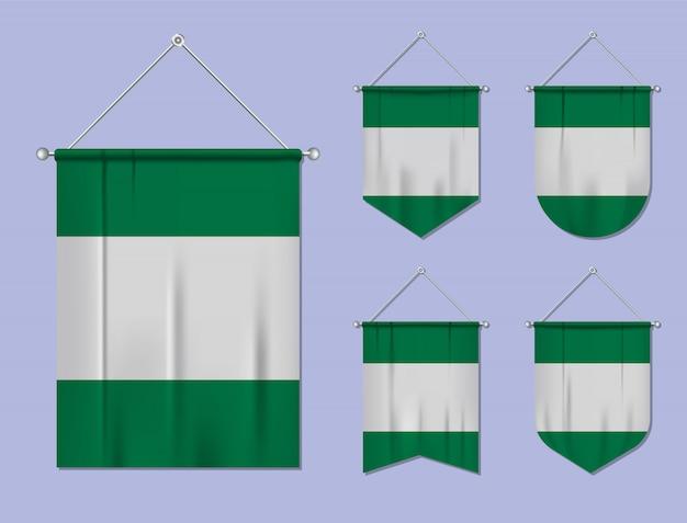 Zestaw wiszących flag nigeria z tekstylną teksturą. różnorodność kształtów kraju bandery. proporczyk pionowy szablon