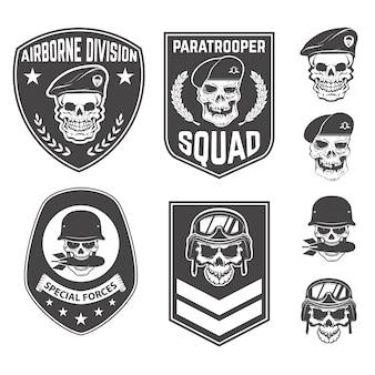 Zestaw wojskowych emblematów i elementów projektu. czaszki z wojskowymi nakryciami głowy. spadochroniarz. dywizja lotnicza.
