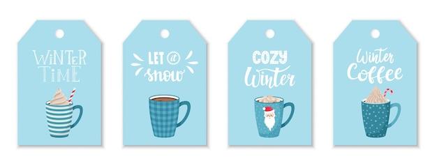 Zestaw zawieszek z niebieskimi kubkami do kawy i kakao z bitą śmietaną oraz napisem odręcznym na temat zimy i kawy. etykiety z napisem odręcznym na niebieskim tle. płaski styl