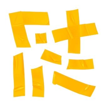 Zestaw żółtej taśmy klejącej. realistyczne żółte kawałki taśmy klejącej do mocowania na białym tle. klej krzyżowy, narożnik i papier klejony.