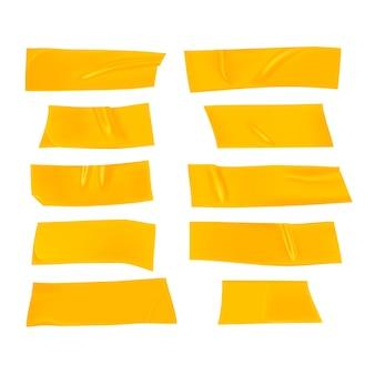 Zestaw żółtej taśmy klejącej. realistyczne żółte kawałki taśmy klejącej do mocowania na białym tle