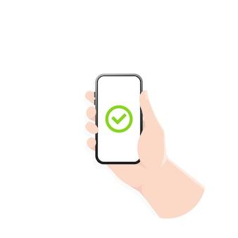 Zielona ikona znacznika wyboru na ekranie smartfona. dłoń trzymająca smartfona z zielonym haczykiem