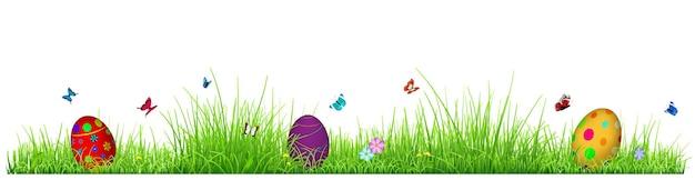 Zielona trawa z jajkami wielkanocnymi, kwiatami i motylami