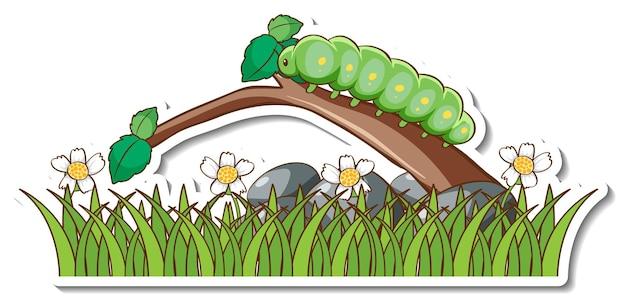 Zielony robak na gałęzi z naklejką na polu trawy