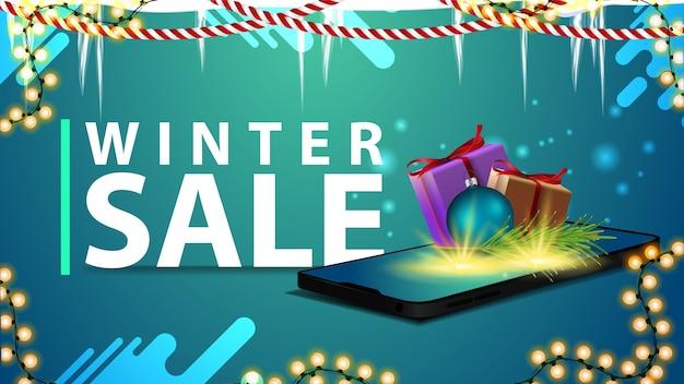 Zimowa wyprzedaż, baner na stronę z girlandami, soplami i smartfonem z ekranu, na którym pojawiają się prezenty