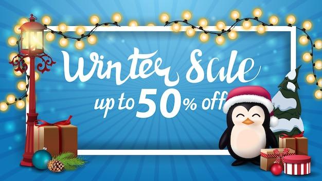 Zimowa wyprzedaż, do 50 zniżki, niebieski baner rabatowy z białą ramką owinięty girlandą, stara latarnia na słupie i pingwin w czapce świętego mikołaja z prezentami