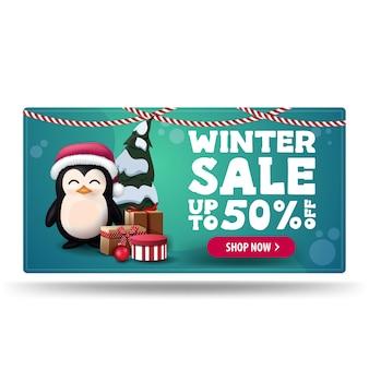 Zimowa wyprzedaż, do 50 zniżki, zielony baner rabatowy z pingwinem w czapce świętego mikołaja z prezentami i różowym guzikiem