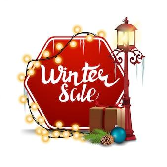 Zimowa wyprzedaż na sześciokątnym znaku z latarnią uliczną i pudełkami prezentowymi