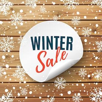 Zimowa wyprzedaż okrągły baner. przywieszka z ceną na podłoże drewniane ze śniegiem i płatkami śniegu. odznaka promocyjna. ilustracji wektorowych.