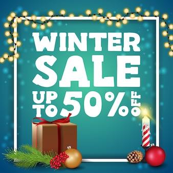 Zimowa wyprzedaż, rabat do 50, zielony baner rabatowy z białą ramką owinięty wianek, prezent i świeczkę