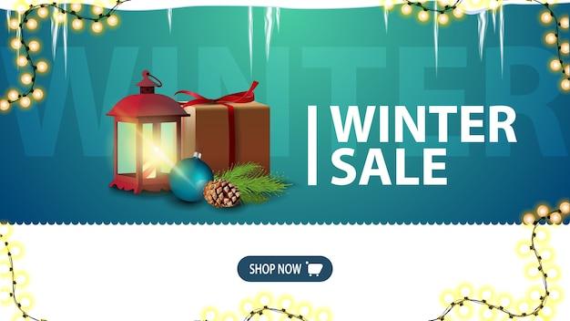 Zimowa wyprzedaż, zielony baner rabatowy na stronę internetową z soplami, girlandą, guzikiem i prezentem z zabytkową lampą