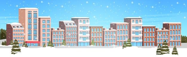 Zimowe budynki miejskie zaśnieżona ulica miasta pejzaż miejski opady śniegu