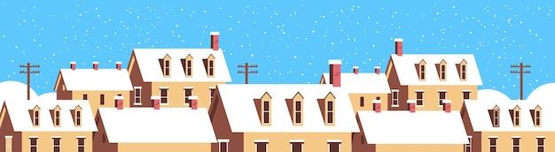 Zimowe domy ze śniegiem na dachach zaśnieżona wioska ulica kartka z życzeniami wesołych świąt płaskie poziome zbliżenie