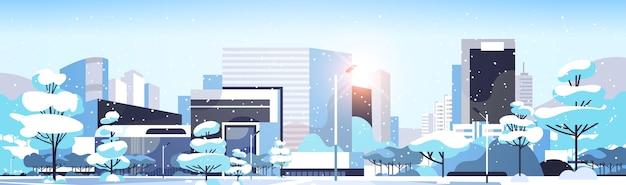 Zimowe miasto zaśnieżone centrum z drapaczami chmur budynki biznesowe słońce pejzaż płaski poziomy wektor ilustracja
