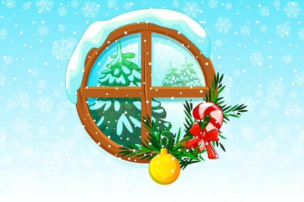 Zimowe okno świąteczne, za którym widoczna jest choinka.