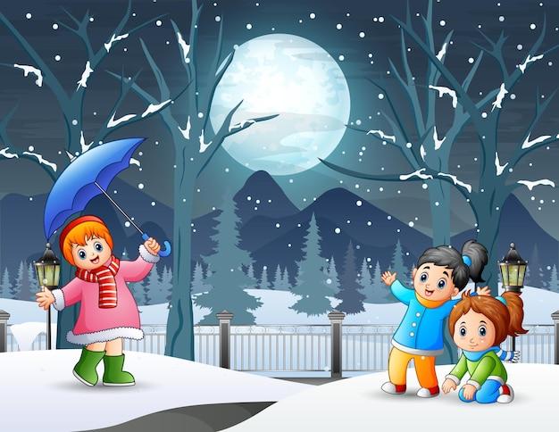 Zimowy nocny krajobraz z dziećmi bawiącymi się na świeżym powietrzu