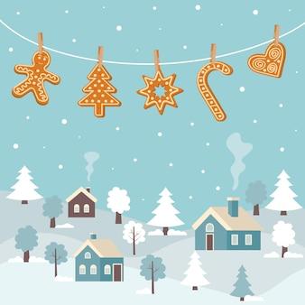Zimowy pejzaż z wiszącymi piernikowymi ciasteczkami przymocowanymi spinaczami do bielizny. kartkę z życzeniami świątecznymi