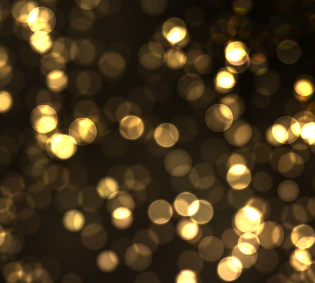 Złocisty bokeh zamazany światło na czarnym tle. złote światła abstrakcyjny blask nieostre migające gwiazdy i iskry.
