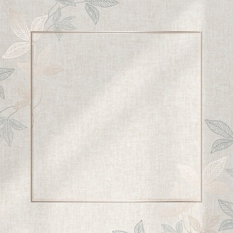 Złota rama z wzorem liści na beżowym tle