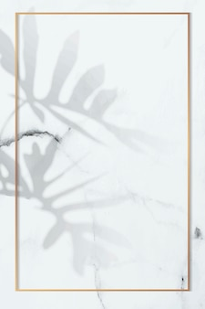 Złota rama z wzorem liścia philodendron radiatum na białym tle marmuru