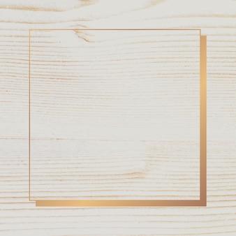 Złota ramka na beżowym drewnianym tle