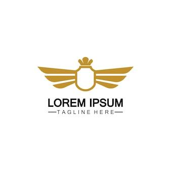 Złota skrzydlata tarcza z logo korony / symbol heraldyki na białym tle
