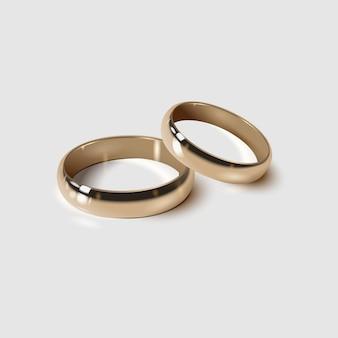 Złote obrączki ślubne na białym tle, realistyczny styl 3d.