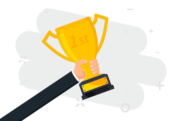Złote trofeum dłoń trzymająca puchar zwycięzców symbol sukcesu zwycięstwo w mistrzostwach