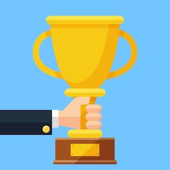 Złoty kubek w dłoni. biznesowe trofeum nagrody płaskie wektor ilustracja kreskówka