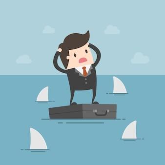 Zmartwiony biznesmen stojąc na teczki w morzu i otoczony przez rekiny.