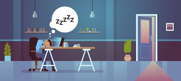 Zmęczony biznesmen śpi w miejscu pracy