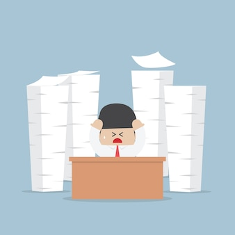 Zmęczony i zajęty biznesmen z stosy pracy do zrobienia