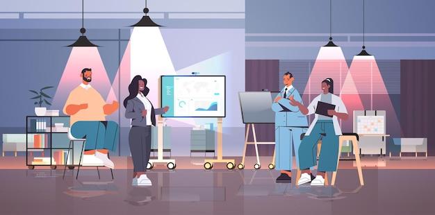 Zmęczony mix wyścig biznesmenów zespół analizujący dane statystyczne na ekranie cyfrowym koncepcja pracy zespołowej ciemna noc wnętrze biurowe poziome pełna długość