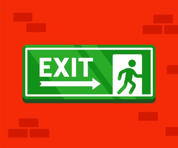 Znak ewakuacji ognia. naklejka bezpiecznego wyjścia wisi na ścianie z cegły.