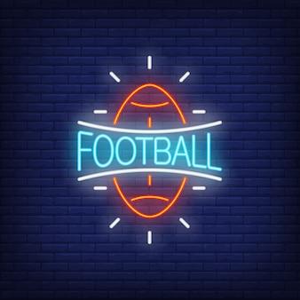 Znak neonowe piłki nożnej. Rugby piłki kształt na ściana z cegieł tle.