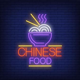 Znak neonowy chińskie jedzenie. puchar gorący kluski z chopsticks na ściana z cegieł tle.