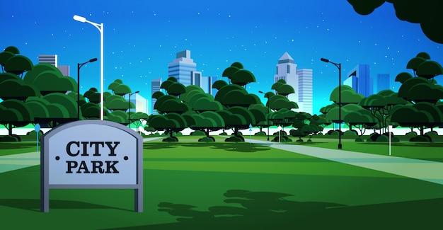 Znak pokładzie noc miasto park skyline skyskraper budynków i ciemne niebo z gwiazdami gród tło