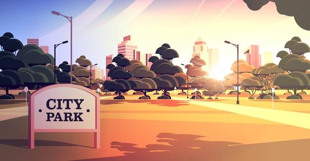 Znak pokładzie w parku miejskim piękny letni dzień panoramę skyskraper budynków zachód słońca pejzaż