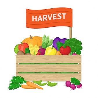Żniwa w drewnianym pudełku z napisem na etykiecie. skrzynia z jesiennymi warzywami. świeża żywność ekologiczna z gospodarstwa. ilustracja jesiennych zbiorów na białym tle.